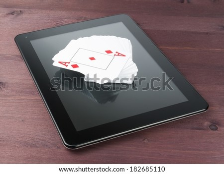 deck of playing cards on digital tablet pc on old wood table, concept of  texas poker online - stock photo