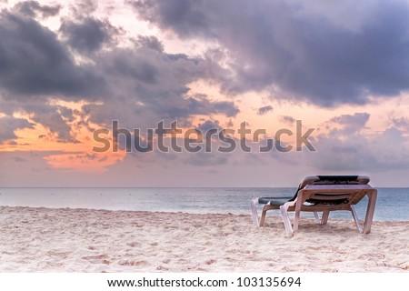 Deckchair on the Caribbean Sea at sunrise - stock photo