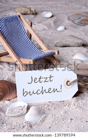 Deckchair, sand and label with lettering book now/beach/holiday
