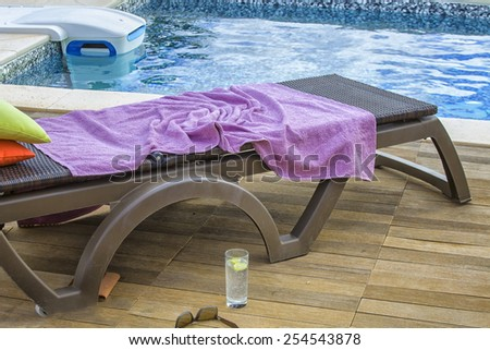 Deckchair with purple towel near swimming pool and a drink and sunglasses - stock photo