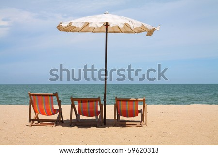 Deckchairs and parasol on the white sand beach facing cha-am beach, Thailand