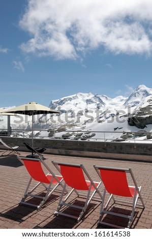 Deckchairs and parasols with view of Monte Rosa in Swiss Alps - stock photo