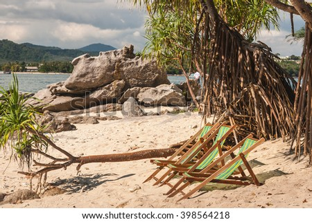 Deckchairs on a beautiful sandy beach with colorful nature on background. Vacation concept.  - stock photo