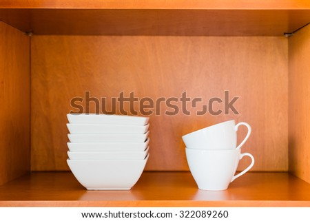 Decluttered minimalistic kitchen cabinet for simple living. Contains only essentials: white porcelain bowls and coffee or tea cups. - stock photo