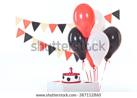 Decor for child's third Birthday. Cake, garland from flags and balloons. Red, black and white colors - stock photo