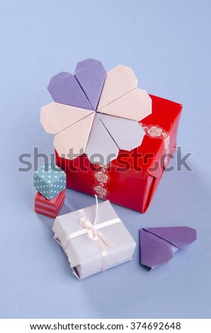 Decor Gift box origami heart with gifts on a purple background - stock photo