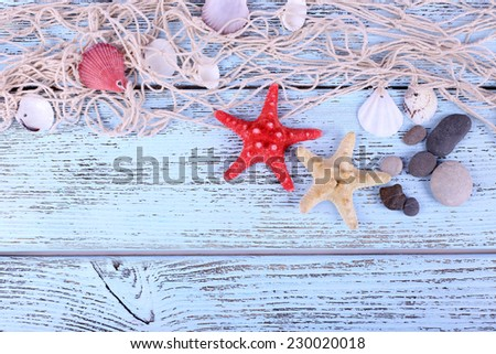 Decor of seashells and seastar close-up on blue wooden table - stock photo