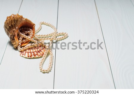 Decor of seashells close-up on blue wooden table. Sea objects - shells, pearls. Background with sea cockleshells and pearls. - stock photo