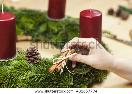 Decorate an advent wreath with cinnamon - stock photo