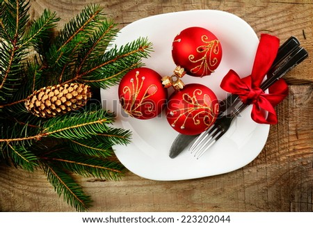 Decorate christmas plate with bauble and pines on wooden surface - stock photo