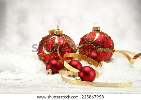 decorate of red balls and golden ribbon on white snow  - stock photo
