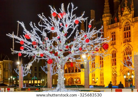 Decorated and illuminated Christmas tree on the rink in front of Province Court at Market Place in the center of Bruges at night, Belgium - stock photo