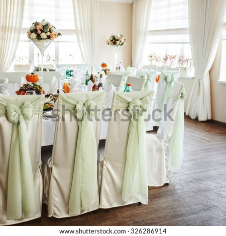 Decorated banquet wedding table with dishware waiting for bride and groom.