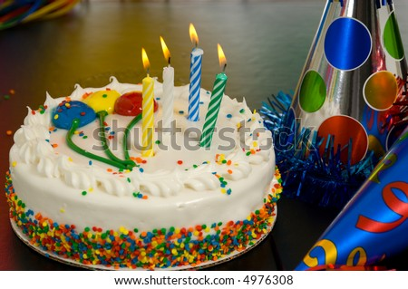 Decorated Birthday cake with candles and party hats - stock photo
