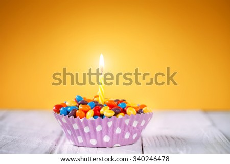 Decorated Birthday cupcake with one lit candle and colorful candies on yellow background Happy birthday card.  - stock photo