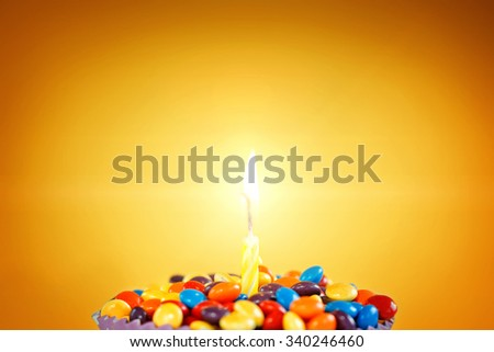 Decorated Birthday cupcake with one lit candle and colorful candies on yellow background. Holidays greeting card. - stock photo