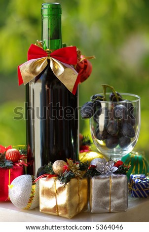 Decorated bottle of red wine with Christmas presents. - stock photo