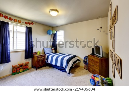 Decorated boys room interior with blue curtains, and stripped blue bedding - stock photo