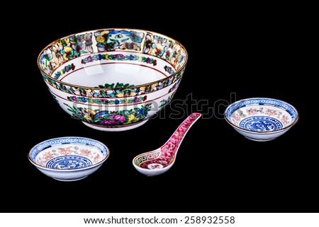 decorated chinese soup bowl  and spoon isolated over a black background - stock photo