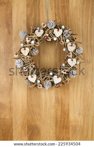 Decorated christmas door wreath with birch hearts and white painted pine cones brown twigs on sapele wood background, copy space - stock photo