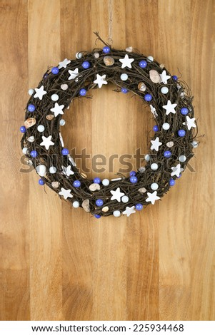 Decorated christmas door wreath with white stars and blue pearls brown twigs on sapele wood background, copy space - stock photo