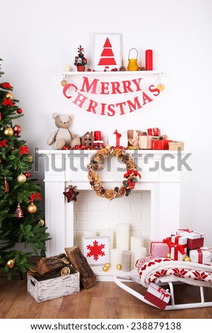 "Decorated Christmas fireplace near fir-tree with inscription ""Merry Christmas"" on white wall background - stock photo"