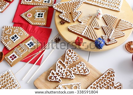 Decorated christmas gingerbread cookies and edcorations on the table. - stock photo