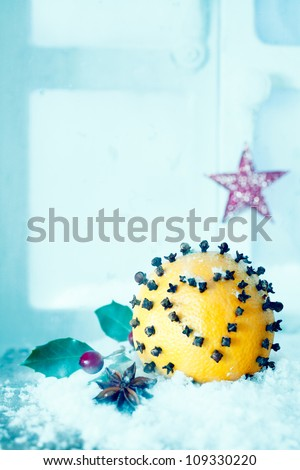Decorated Christmas orange covered in spicy cloves forming a heart shape with copyspace to celebrate Xmas or Valentines day - stock photo