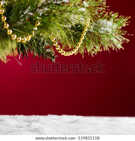 decorated christmas tree and snow on red background - stock photo