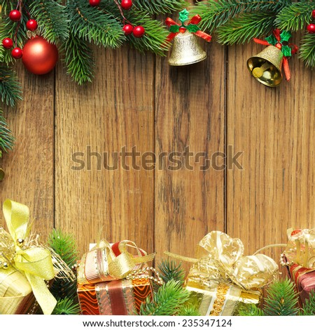 Decorated Christmas tree border on wood paneling with gold baubles and bells, a decorative Xmas gift wrapped in a golden bow, holly and beads with copyspace for your seasonal greeting - stock photo
