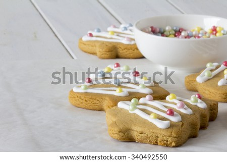 Decorated Christmas Tree Cookies with Bowls of Sugar Pearls - Copy Space Selective Focus - stock photo