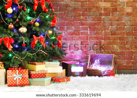 Decorated Christmas tree on brick wall background - stock photo