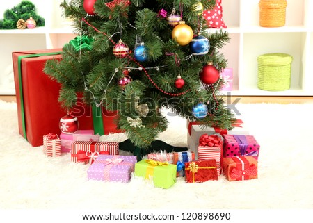 Decorated Christmas tree on home interior background - stock photo