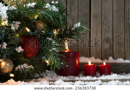 Decorated Christmas tree with burning candles on a wood background - stock photo