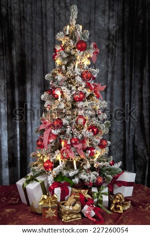 Decorated christmas tree with electric candles and presents - stock photo