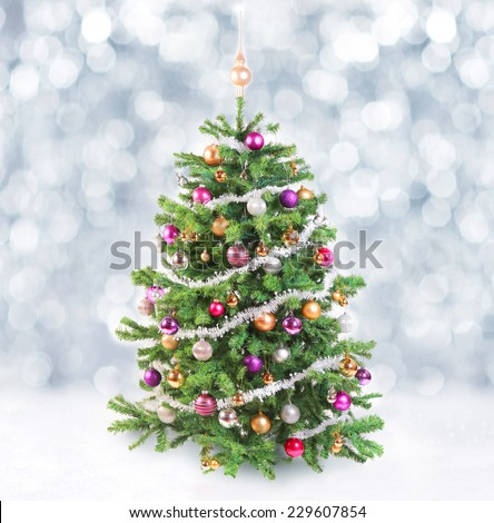 Decorated colorful artificial spruce Christmas tree with garlands of silver tinsel and silver, gold and purple baubles in a bokeh of falling snowflakes and winter snow - stock photo