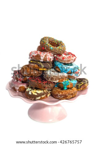 Decorated colorfull donuts with sweets on a pile isolated over white