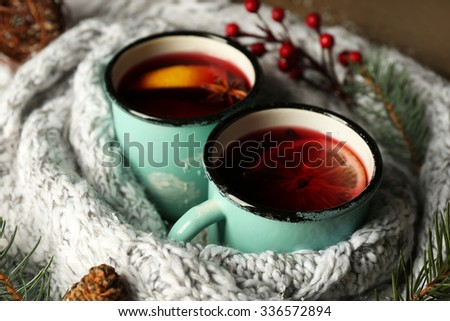 Decorated composition of mugs with mulled wine in knitted scarf, close up - stock photo