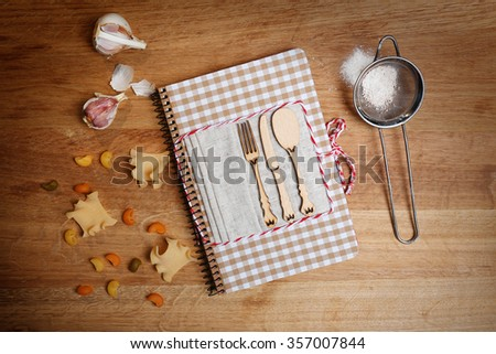 Decorated cookbook on wooden background - stock photo