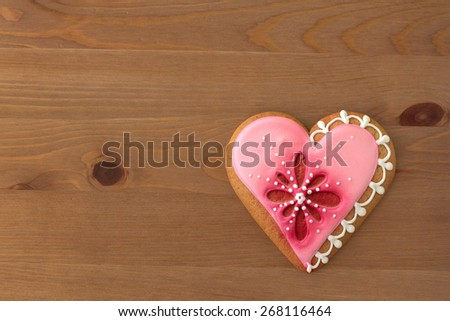 Decorated cookie in the shape of heart on a wooden table - stock photo