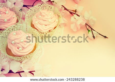 Decorated cupcakes with spring flowers. - stock photo