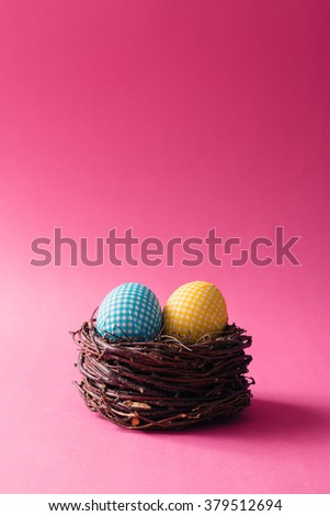 Decorated Easter eggs in nest on pink background - stock photo