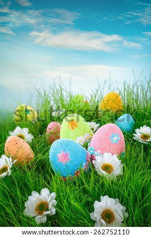 Decorated easter eggs in the grass on blue background - stock photo