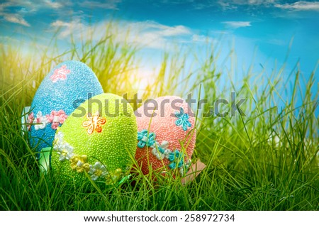 Decorated easter eggs in the grass on blue sky background - stock photo