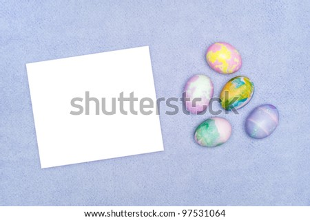 Decorated Easter eggs on purple cloth with a blank white card for placement of copy. - stock photo