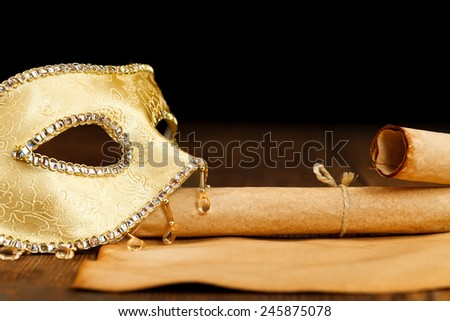 Decorated golden carnival mask with old paper scrolls - stock photo