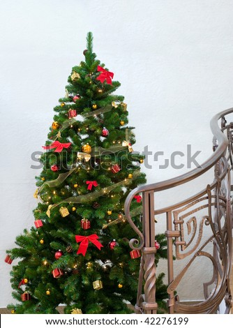decorated green Christmas tree near forged curved handrail of stairs leading to the upstairs - stock photo