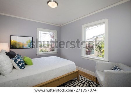 Decorated grey bedroom with amazing wooden bed frame and expensive chair, big expansive mattress with pillows in modern home.  - stock photo