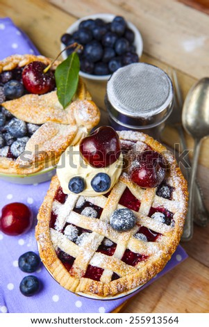 Decorated homemade shortcrust pastry berry pies with polka dot cloth, shiny metal icing sugar shaker, spoon, fork and selection of berries on grunge style wooden table - stock photo