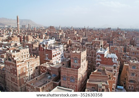 Decorated houses, palaces, minarets and the Saleh Mosque in the fog, the Old City of Sana'a, Republic of Yemen, Unesco world heritage site with unique architectural characteristics